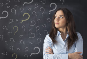 Young woman thinking with blackboard